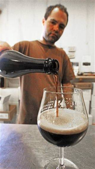 In this Wednesday, April 3, 2013 photo, brewer Shaun Hill pours a fresh brew at Hill Farmstead Brewery in Greensboro, Vt. Vermonters are buzzing about beer, and with good reason. The craft brew world has noticed that the small New England state better known for its cheeses and maple syrup also happens to make killer beer. In fact, one brewery, Hill Farmstead Brewery, has been rated the world's best brewer on a popular international consumer review website called RateBeer.com. (AP Photo/Toby Talbot)