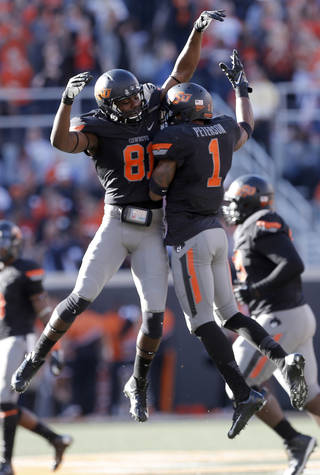 Oklahoma State's Kevin Peterson (1) celebrates his interception with Oklahoma State's Jhajuan Seales (81) during a college football game between the Oklahoma State University Cowboys (OSU) and the University of Kansas Jayhawks (KU) at Boone Pickens Stadium in Stillwater, Okla., Saturday, Nov. 9, 2013. Photo by Sarah Phipps, The Oklahoman