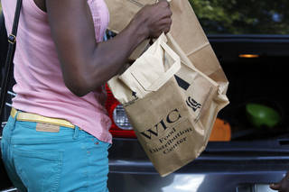 A recipient of the Special Supplemental Nutrition Program for Women, Infants and Children, better known as WIC, loads food into her car after leaving a center in Jackson, Miss., Thursday, Oct. 3, 2013. (AP Photo/Rogelio V. Solis)