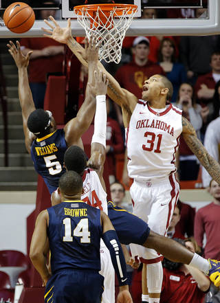 Oklahoma's D.J. Bennett (31) defends a shot by West Virginia's Devin Williams (5) during the college basketball game between the University of Oklahoma Sooners (OU) and West Virginia University Mountaineers (WVU) at the Lloyd Noble Center in Norman, Okla. on Wednesday, March 5, 2014. Photo by Chris Landsberger, The Oklahoman