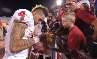 Oklahoma's Kenny Stills (4) signs autographs for fans during the college football game between the University of Oklahoma Sooners (OU) and the University of Kansas Jayhawks (KU) on Sunday Oct. 16, 2011 in Lawrence, Kan. Photo by Chris Landsberger, The Oklahoman