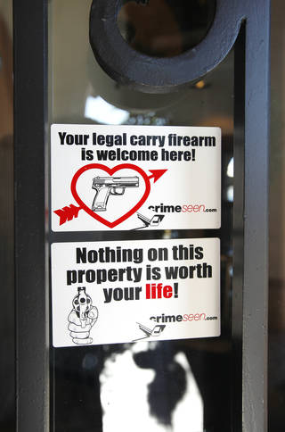 Stickers on the front door of Casa De Los Milagros Mexican Restaurant and Cantina in Oklahoma City communicate the establishment's firearms policy. PAUL B. SOUTHERLAND - PAUL B. SOUTHERLAND