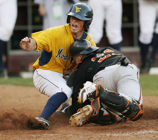 West Virginia's Bobby Boyd (4) looks to see if he is safe after sliding home to score the winning run against Oklahoma State catcher Victor Romero (31) in the tenth inning during an NCAA baseball game between Oklahoma State and West Virginia in the Big 12 Baseball Championship tournament at the Chickasaw Bricktown Ballpark in Oklahoma City, Saturday, May 25, 2013. WVU beat OSU 6-5 in ten innings. Photo by Nate Billings, The Oklahoman