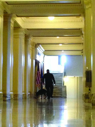 A law enforcement officer and what appears to be a bomb-sniffing dog are seen Friday in a hall at the Capitol. PHOTO BY ZEKE CAMPFIELD, THE OKLAHOMAN