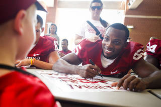 FANS / COLLEGE FOOTBALL: OU wide receiver Ryan Broyles smiles as he signs a poster for Carson Jackson of Moore at the University of Oklahoma's Meet the Sooners Day at Gaylord Family - Oklahoma Memorial Stadium in Norman on Saturday, August 6, 2011. Photo by Zach Gray ORG XMIT: KOD