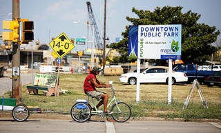 A man rides past property on the corner of SW 3rd and Hudson on Thursday. The city has filed an eminent domain suit for MAPS park use. Photo by Bryan Terry, The Oklahoman