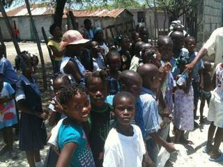 Haitian children, survivors of last year's devastating earthquake, await donated school supplies during Mark Stansberry's recent visit to their country. PHOTO PROVIDED