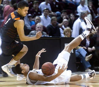 Texas A&M's Jordan Green falls to the court after being fouled by Oklahoma State's C.J. Guerrero during the first half of an NCAA college basketball game at Reed Arena in College Station, Texas, Saturday, Jan. 28, 2012. (AP Photo/Bryan-College Station Eagle, Stuart Villanueva) ORG XMIT: TXBRY102