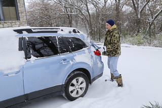 Kevin Farmer clears snow from his car in the Arrowhead Hills addition in Edmond Friday, December 6, 2013. Photo by Doug Hoke, The Oklahoman
