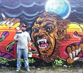 Robert Levering poses in front of a Halloween-themed piece he and other artists painted in October in Moore. PHOTO PROVIDED