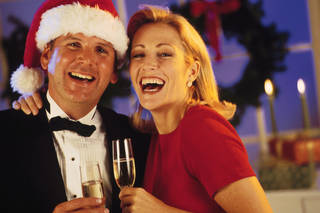 Couple in formal attire celebrating holidays with champagne