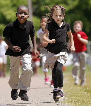 First graders Tequan Ligons, left, and Kira Setliff run on the school track at Monroe Elementary as part of their participation in this year's Kid's Marathon. More than 120 students from Monroe Elementary School in Oklahoma City will finish the final 1.2 miles of the Kid's Marathon during the Oklahoma City Memorial Marathon on Sunday. Tuesday, April 24, 2012. Photo by Jim Beckel, The Oklahoman