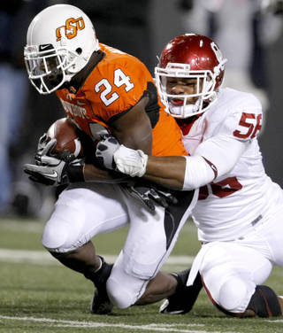 Oklahoma's Ronnell Lewis (56) brings down Oklahoma State's Kendall Hunter (24) during the Bedlam college football game between the University of Oklahoma Sooners (OU) and the Oklahoma State University Cowboys (OSU) at Boone Pickens Stadium in Stillwater, Okla., Saturday, Nov. 27, 2010. Photo by Bryan Terry, The Oklahoman