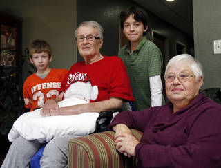 Bob Matthews and his wife, B. J., along with their grandsons Jack Collins, left, and Ethan Collins, talk about Bob's long road of recovery after contracting West Nile virus in the summer. Bob Matthews said his grandsons are his best friends and have been helpful at raising his spirits during his recovery. PHOTO BY PAUL HELLSTERN, THE OKLAHOMAN