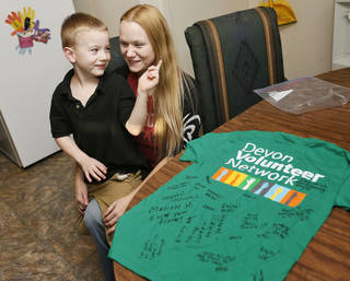 Camryn Redwine, 5, sits in the lap of his mother, Brittani Swain, near a T-shirt signed by volunteers from framing day for their house, which they bought from Central Oklahoma Habitat for Humanity. The house is on Durland Way in Habitat's Hope Crossing addition at NE 83 and Kelley Avenue. NATE BILLINGS - The Oklahoman
