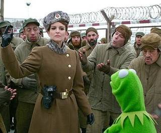 "Kermit the Frog is confronted by Tina Fey in a Russian Gulag in ""Muppets Most Wanted."" On the far right is Danny Trejo and, to the left of Trejo, Ray Liotta, two familiar actors who often play movie villains. (Disney)"