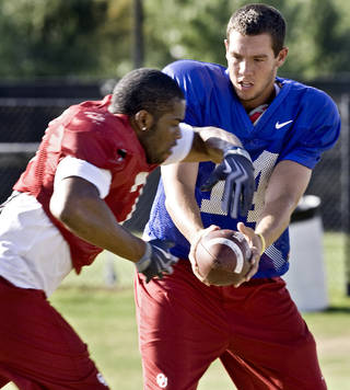 Sam Bradford hands the ball off to DeMarco Murray during OU's practice on Monday. Photo by Chris Landsberger, The Oklahoman