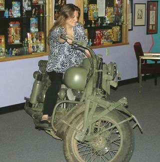 Jodi Wood, manager of the Toy and Action Figure Museum, sits on one of the cycles used in the 2011 Captain America movie. (Pauls Valley Daily Democrat photo)