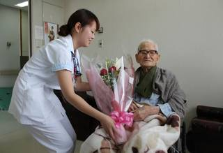 """This picture taken by the Kyotango City Government on December 26, 2012 shows the world's oldest man Jiroemon Kimura (R) receiving a flower bouquet from a nurse at a hospital in Kyotango, Kyoto prefecture in western Japan. The world's oldest person and the oldest man Kimura died of natural causes in a hospital in Kyotango on June 12, 2013 at the age of 116. AFP PHOTO / FILES / KYOTANGO CITY GOVERNMENT ---EDITORS NOTE---RESTRICTED TO EDITORIAL USE - MANDATORY CREDIT """"AFP PHOTO / KYOTANGO CITY GOVERNMENT"""" - NO MARKETING NO ADVERTISING CAMPAIGNS - DISTRIBUTED AS A SERVICE TO CLIENTSKYOTANGO CITY GOVERNMENT/AFP/Getty Images"""