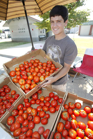 Kyle Kanaly, 14, shows off the tomatoes he grew and sells at the Junior Market at Edmond's Festival Market Place. PHOTO BY DAVID MCDANIEL, THE OKLAHOMAN