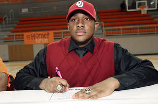 Dominique Alexander, who signed his letter of intent to attend the University of Oklahoma, signs with others from Booker T. Washington High School, inside the Nathan E. Harris Field House at Booker T. Washington High School, on National Signing Day, Wednesday, Feb. 6, 2013. CORY YOUNG/Tulsa World