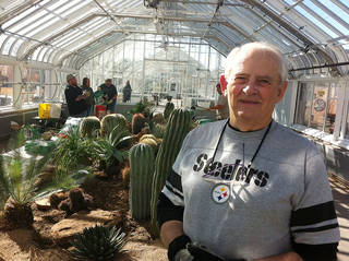 Tony Furrh, of Oklahoma City, volunteers helping set up the desert display at the new Ed Lycan Conservatory at Will Rogers Gardens Photo by Robert Medley