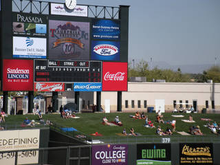 Sunbathers lounge beneath the scoreboard at Surprise Stadium in Surprise, Ariz., during a game between the San Francisco Giants and the Kansas City Royals. Photo courtesy of Patricia Arrigoni.