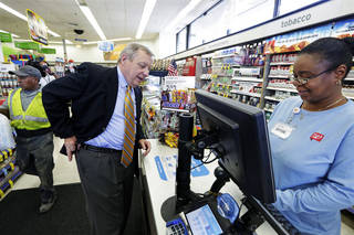U.S. Sen. Dick Durbin, D-Ill., talks to Walgreens clerk Estella Washington as he shops after a news conference Wednesday in Chicago. AP Photo M. Spencer Green - AP