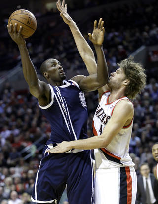 OKC's Serge Ibaka, left, shoots against Portland's Robin Lopez during first-half action on Tuesday night. AP Photo