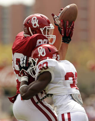 Connor Knight is hit just as he touches a pass by Thaddeus LaGrone during the Spring College Football Game of the University of Oklahoma Sooners (OU) at Gaylord Family-Oklahoma Memorial Stadium in Norman, Okla., on Saturday, April 12, 2014. The pass was incomplete. Photo by Steve Sisney, The Oklahoman