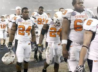 Deron Fontenot, left, Kendall Hunter, and David Washington of OSU walk off the field after their loss during the Holiday Bowl college football between Oklahoma State and Oregon at Qualcomm Stadium in San Diego, Tuesday, Dec. 30, 2008. PHOTO BY BRYAN TERRY, THE OKLAHOMAN. ORG XMIT: KOD