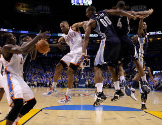Oklahoma City's Russell Westbrook (0) passes the ball to Kendrick Perkins (5) from between Zach Randolph (50) of Memphis and Darrell Arthur (00) during game two of the Western Conference semifinals between the Memphis Grizzlies and the Oklahoma City Thunder in the NBA basketball playoffs at Oklahoma City Arena in Oklahoma City, Tuesday, May 3, 2011. Photo by Bryan Terry, The Oklahoman
