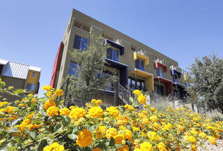 This June 4, 2014 photo shows homes within the newly built Portland townhouse development in Phoenix. Americans increasingly say they prefer to live near the centers of cities and towns, where commutes tend to be easier and culture, restaurants and entertainment close by. It marks a pronounced shift away from the yearning for open suburban space that drove U.S. home construction for decades. (AP Photo/Matt York)