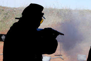 """""""Major Missalot"""", aka Ted Hoversen, from Tecumseh, Mo., fires a shotgun at a target during the Land Run, the biggest cowboy action shoot of the year Friday at the Oklahoma City Gun Club. Photo By Paul Hellstern, The Oklahoman"""