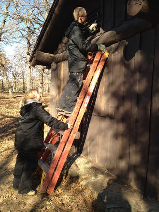 Team members Steven McKenzie and Christina Kloha scrape the exterior of a cabin at Lake Murray State Park. PHOTO BY CAROL SCHNEIDER PROVIDED.