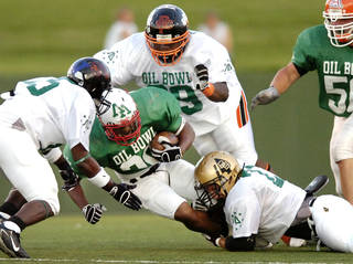 Oklahoma defenders, from left, Durell Parker, Tony Gillespie and Mitchell Bailey bring down Texas running back Dreu Ashley on Saturday, June 21, 2008, during the second quarter of the Oil Bowl football game in Wichita Falls, Texas. (AP Photo/Wichita Falls Times Record News, Jeffrey Haderthauer)