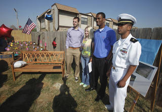 DEDICATE / DEDICATED / SPC. JASON HUNT: Landry Jones and Julian Wilson, University of Oklahoma football players; stand with Jennifer Hunt, widow of Spc. Jason D. Hunt; and Navy officer candidate James Smith at the dedication of Quinton Carter's charity educational garden at KinderCare on Friday, March 25, 2011, in Norman, Okla. Photo by Steve Sisney, The Oklahoman