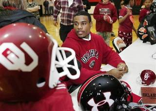 Dewar defensive back Ronell Lewis was the center of attention after he signed letter of intent to play football at the University of Oklahoma during a school-wide assembly in the school's gym Wednesday morning, February 4, 2009. For nearly an hour after he inked the letter, he was still in the gym sugning autographs, shaking hands and posing for pictures with fans that ranged from babies to retired townspeople. BY JIM BECKEL