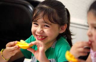 Miracle Medrano, 7, laughs while eating an orange with a few of her friends. The girls are among dozens of children who are receiving healthy snacks and meals through a summer feeding program for children. Novo Ministries partners with the Regional Food Bank Of Oklahoma to feed the children during the summer months while they are out of school. These children are at Ambassador Courts Community Center. JIM BECKEL - THE OKLAHOMAN