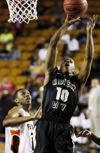 Midwest City's Torey Noel, right, shoots against Putnam City during a March 2013 game. Noel is the Bombers' leading scorer.