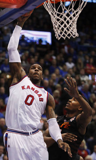 Kansas forward Thomas Robinson (0) makes a basket while covered by Oklahoma State guard/forward Le'Bryan Nash, right, during the first half of an NCAA college basketball game in Lawrence, Kan., Saturday, Feb. 11, 2012. Robinson scored 24 points in the game. Kansas defeated Oklahoma State 81-66. (AP Photo/Orlin Wagner) Orlin Wagner