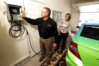 Dan Reeves of Landmark Fine Homes and Pam Hall of Oklahoma Natural Gas fill a CNG vehicle in the garage at the Landmark model home at 4500 Northfields in Norman.
