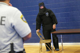 Wearing a protective suit, Master Sgt. Blake Webster with the Oklahoma City Police Department goes through a Taser training exercise with Sgt. Shawn Byrne. PHOTO BY BRYAN TERRY, THE OKLAHOMAN