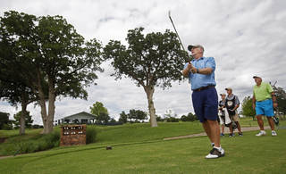 Lee Symcox, an Oklahoma City native, tees off on a hole near temporary buildings that have been erected on the course at Oak Tree National Country Club in preparation for the 2014 U.S. Senior Open, held in July, on June 12, 2014. Photo by KT King/The Oklahoman