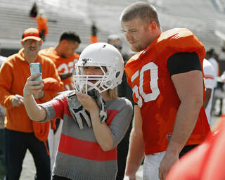 Oklahoma State sophomore Hunter Bell takes a photo of herself with OSU's Zac Veatch after Oklahoma State's Orange Blitz football practice at Boone Pickens Stadium in Stillwater, Okla., Saturday, April 5, 2014.