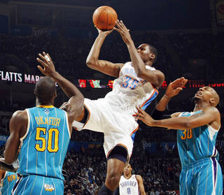 Oklahoma City's Kevin Durant (35) takes a shot between Emeka Okafor (50) and David West (30) of New Orleans during the NBA basketball game between the New Orleans Hornets and the Oklahoma City Thunder at the Oklahoma City Arena in downtown Oklahoma City, Monday, Nov. 29, 2010. Photo by Nate Billings, The Oklahoman