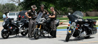 Above and right: Oklahoma Highway Patrol troopers talk about motorcycles bought for a safety and educational program. Photos by Tiffany Gibson, The Oklahoman