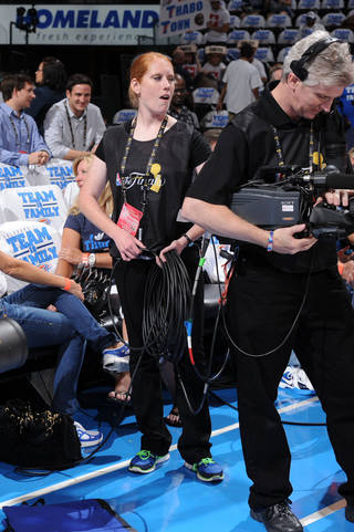 Army Reserve Spc. Elizabeth Fowler, of Oklahoma City, helps an NBA cameraman during a Finals game at the Chesapeake Energy Arena last week. PHOTO BY ANDREW D. BERNSTEIN / NBAE