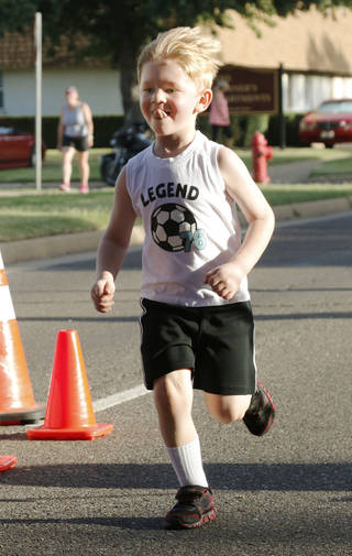 Rexton Potter, 4, crosses the finish line of the one-mile fun run of the Fine Arts Institute of Edmond's annual 5K to Monet event. PHOTO BY PAUL HELLSTON, THE OKLAHOMAN PAUL HELLSTERN - Oklahoman