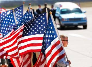 MILITARY / SOLDIER'S REMAINS / FORT SILL: Patriot Guard Riders hold American flags near the hearse as they await the arrival of the plane carrying the soldier's casket. The remains of U.S. Army SSgt. Travis Tompkins arrived in a flag-draped casket on a small jet that arrived at Henry Post Army Airfield on Ft. Sill around 12 :45 Wednesday afternoon, March 23, 2011. He died March 16 of wounds sustained in an attack the previous day when enemy forces attacked his unit in Afghanistan with a rocket-propelled grenade. His funeral is scheduled for Friday. Photo by Jim Beckel, The Oklahoman ORG XMIT: KOD